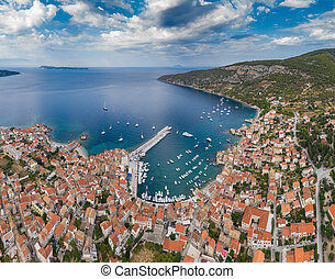 Aerial panoramic view of city Komiza - the one of numerous port towns in Croatia, is a lot of moored sailboats of a regatta, orange roofs of houses, a cathedral St.Nicholas, beach Gusarica, Vis, Milna