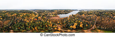 Aerial panoramic view of lake and colorful forests on a autumn day in Finland. Drone photography