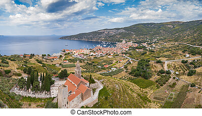 Aerial panoramic view of the cathedral St.Nicholas in Komiza city - the one of numerous port towns in Croatia, orange roofs of houses, picturisque bay, mountain is on background