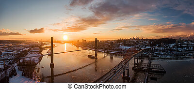 Aerial Panoramic View of the Modern City, Bridge and Fraser River during a colorful Sunset