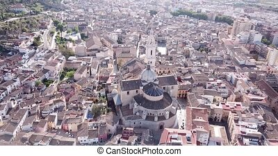 View from drone of Roman Catholic Basilica in Spanish town of Xativa on background of residential areas