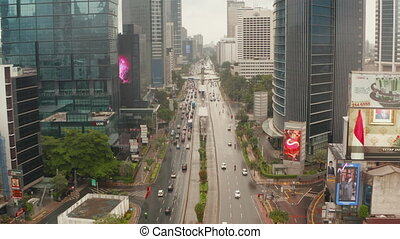 Aerial pedestal tilting shot of vehicles on a multi lane motorway in modern city center of Jakarta 4K