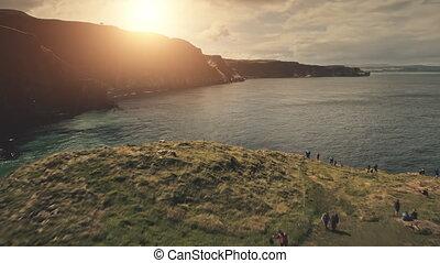 Aerial people on sun ocean shore. Tourists at sea bay with cliff coast. Nature seascape at Irish landmark. Rock isle landscape with travelers. Carrick Island, Northern Ireland, United Kingdom, Europe