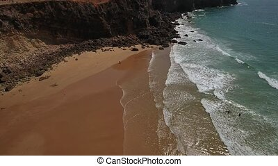Aerial. People walk on the beach rocky shore. Sagres.