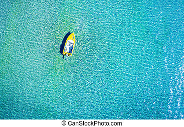 Aerial photo of motorboat tied up in turquoise sea water, Greece