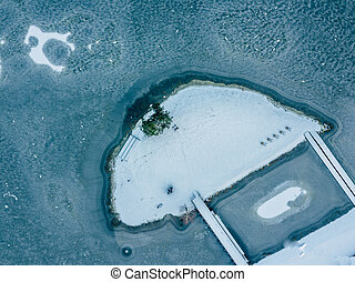Aerial Photography of an Island Covered in Snow with a Frozen Lake around it