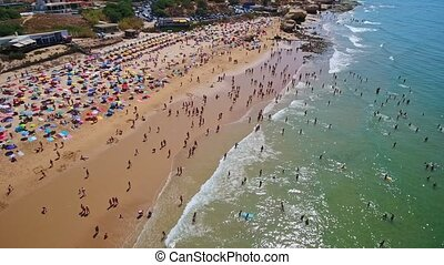 Aerial photography of the coast, the beaches of Gale in Portugal. Tourists are resting. The movement is parallel to the shore