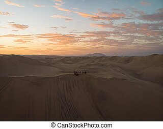 Aerial postcard panorama sunset view of buggy tour grop on dry sand dunes desert of Huacachina Ica Peru South America