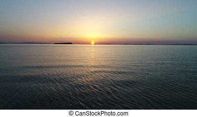 Aerial retreat view of calm ocean at sunset - aerial drone...
