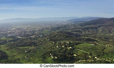 Aerial revealing shot of distant city of Florence, Italy -...