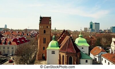 Aerial rising shot of church in old town and new buildings of Warsaw, Poland. 4K video