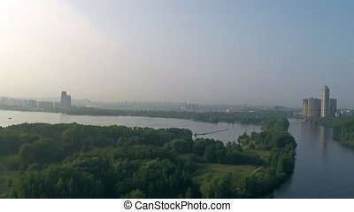 Aerial rising shot of Moscow river, bridge, forest and distant luxury residential houses