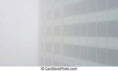 Aerial rising shot of office building in fog - Aerial shot...