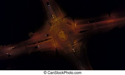 Aerial rising time lapse of a car road roundabout at night