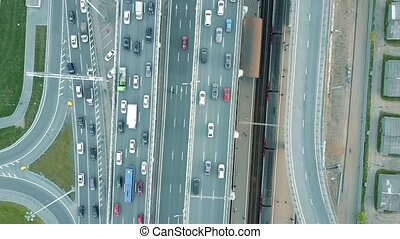 Aerial rising top down view shot of traffic jam on a highway and moving train in the rush hour. 4K clip