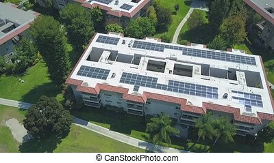 Aerial rising view, rooftop apartment complex solar panels, ...