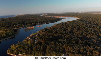Aerial river Lielupe into Baltic sea gulf in Varnukrogs - Golden Hour sunset top view from above - Drone shot with evergreen pine seaside forest visible in the background - Balta Kapa in European Latvia. - Cinematic professional panning with ND and PL filters used