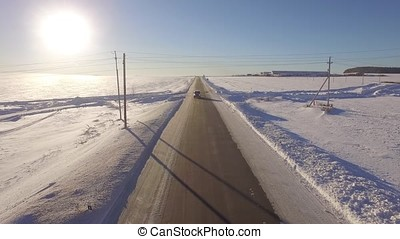Aerial Roadways. Suv driving in white snowy evergreen forest on slippery asphalt road. Aerial view of the road and the fields in the winter