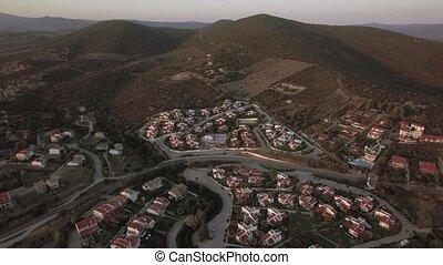 Aerial scene of neighbourhood and green hills in Trikorfo...