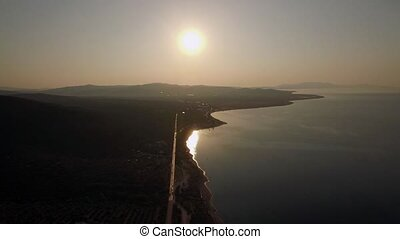 Aerial scene of shoreline and green upland at sunset, Greece...