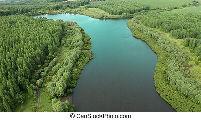 Aerial scenery of forest lake from a drone flying forward -...