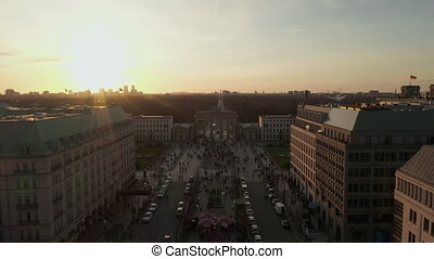 AERIAL Scenic low flight through busy Berlin, Germany Street revealing Brandenburg Gate in beautiful epic sunset light 4K