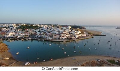 Aerial. Shooting from sky of Portuguese tourist city Ferragudo, view of the dock and beaches.