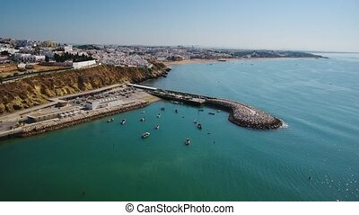 Aerial. Shooting from sky of Portuguese tourist city of Lagos, overlooking dock and the beaches.