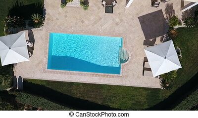 Aerial. Shooting from sky with a drone, a pool near house in the garden.