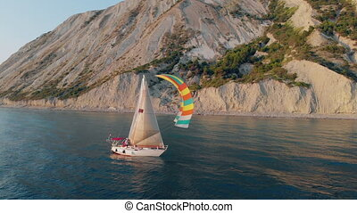 Aerial shooting of a sailing yacht in the sea. Sunny day at sea. Man sailing on yacht at the sea
