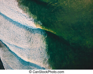 Aerial shooting of big stormy waves at sunset. Background with ocean wave