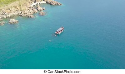 Aerial shot blue sea with sailing boat and swimming people in turquoise water. Drone view people bathing around boat sailing in blue lagoon. Sea aerial view.