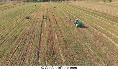 Aerial shot from top to down of tractor cutting grass and...