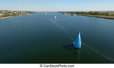 Aerial shot of a beautiful blue yacht sailing in the Dnipro sparkling blue waters