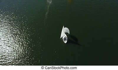 Aerial shot of a beautiful white yacht with two sails, one mast floating slowly