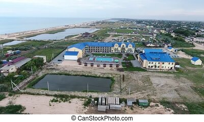 Exciting bird`s eye view of a large hotel complex with a swimming pool inside on a sea resort at the Black Sea coastline on a sunny day in summer.
