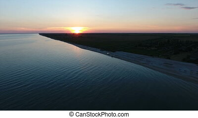 Aerial shot of a  big yellow sun at sunset over an island in the Black Sea