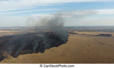 Aerial shot of a black area of burning wetland in the Dnipro...