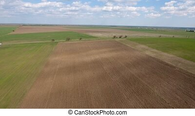 Aerial shot of a brown plowed field leading to a country highway in spring