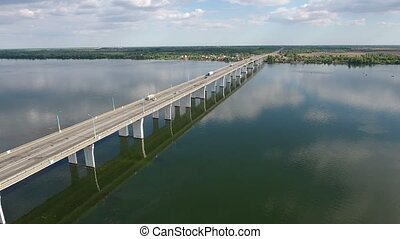 Aerial shot of a car bridge over the Dnipro with a drone flying along it