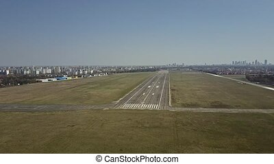 Aerial shot of a city airport plated runway on a sunny day