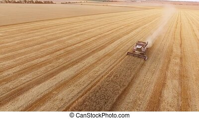 Aerial shot of a combine harvester reaping crops askew on a...