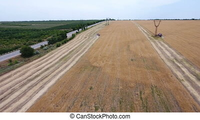Aerial shot of a combine harvester reaping ripe wheat near a...