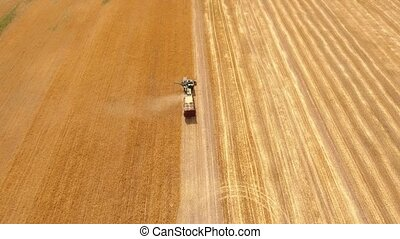 Aerial shot of a combine harvester reaping ripe wheat on a...