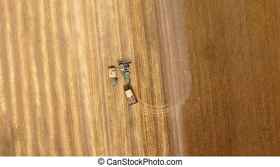 Aerial shot of a combine loading grain in a truck back on a...