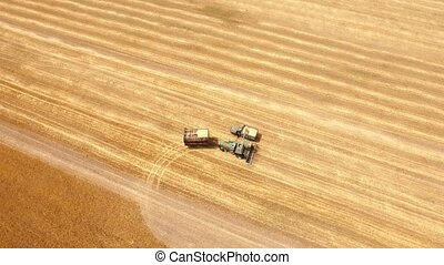 Aerial shot of a combine reloading grain to two trucks on a...