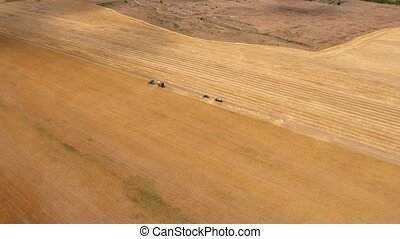 Aerial shot of a combine with a trailer for straw and trucks...
