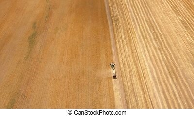 Aerial shot of a combine with a trailer holding straw on a...