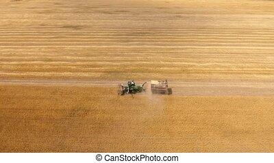 Aerial shot of a combine with a trailer reaping wheat on a...