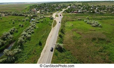 Aerial shot of a country highway leading to a small village in Eastern Europe